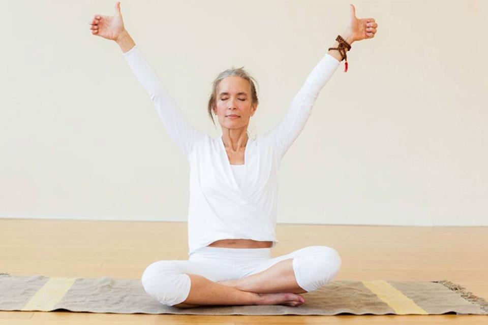 Women in Kundalini Yoga pose on mat