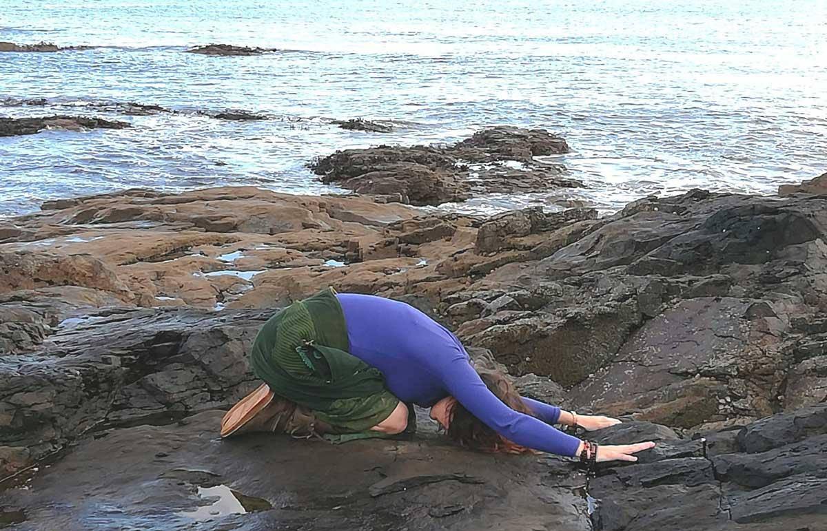 Sarah Jones in yoga pose on rocks in front of sea.